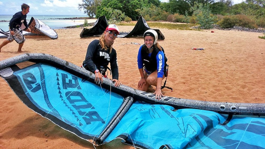 Show item 1 of 8. setting up the kiteboard with instructor in Maui