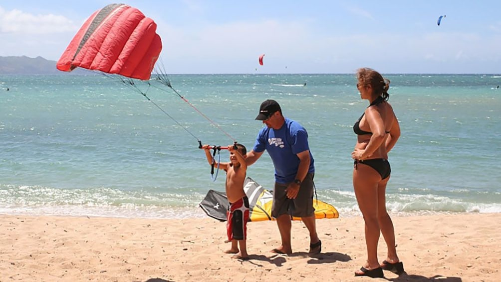 Show item 3 of 8. Child on the beach with a kite in Maui