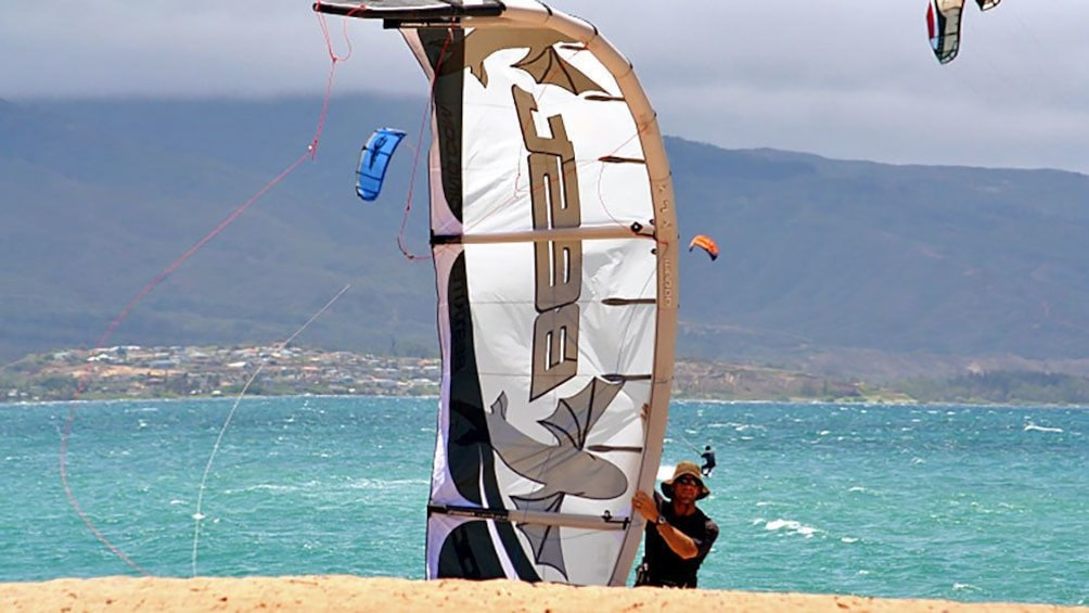 Show item 3 of 8. man brining kiteboard back to shore in Maui
