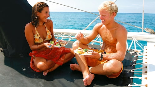 Couple eating lunch on a black rubber trap on the ship for the Deluxe Molokini Snorkel in Maui