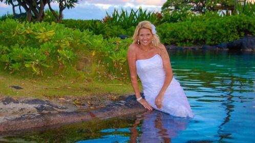 woman sitting on edge of water in Kauai