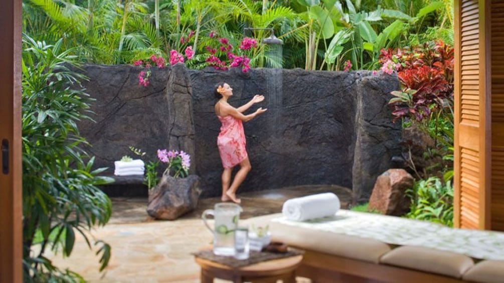Show item 1 of 6. woman stepping under shower at Anara Spa in Kauai