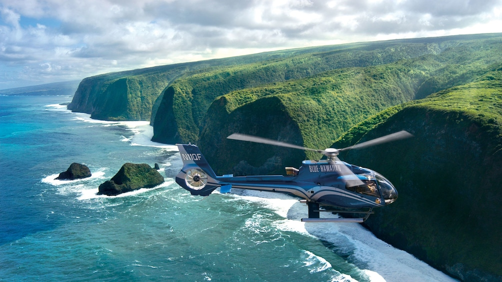 Show item 9 of 9. Helicpter flying over Cliffs on the shore on the Big Island of Hawaii