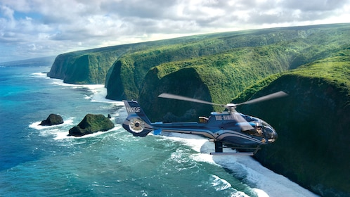 Helicpter flying over Cliffs on the shore on the Big Island of Hawaii
