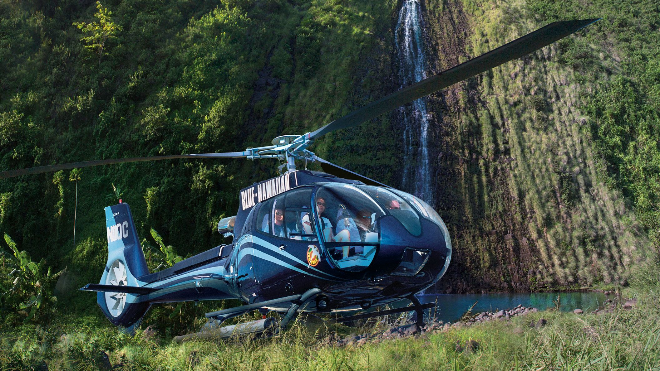 Helicopter landed by a water fall on the Big Island on Hawaii