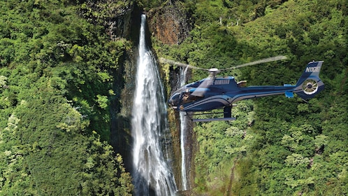 helicopter flying over waterfall in Kauai
