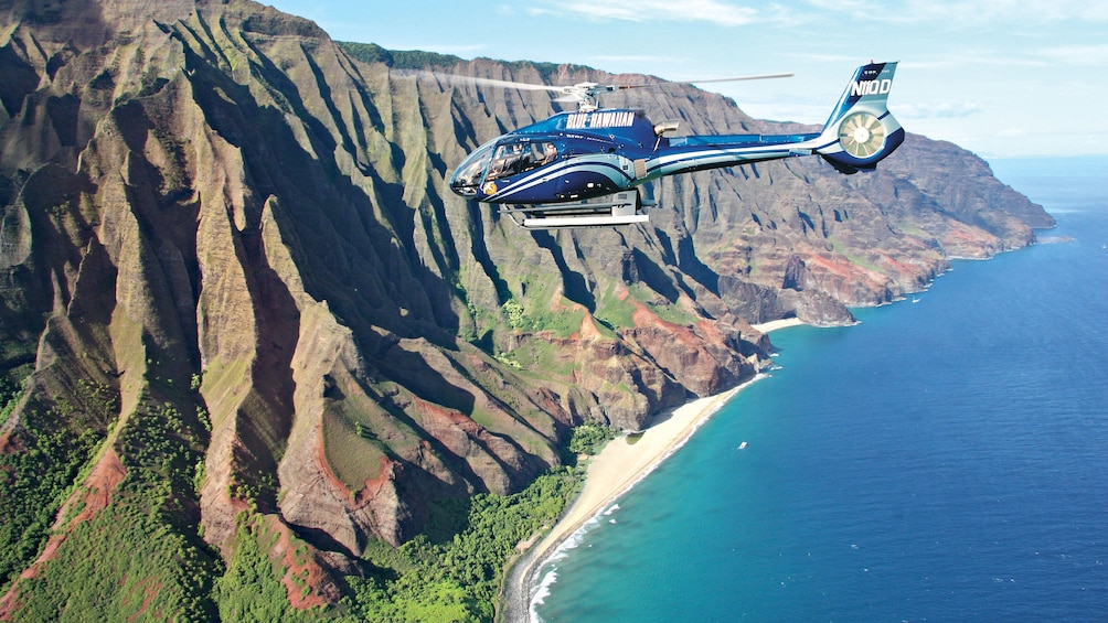 Show item 3 of 5. helicopter flying over mountain ridges in Kauai