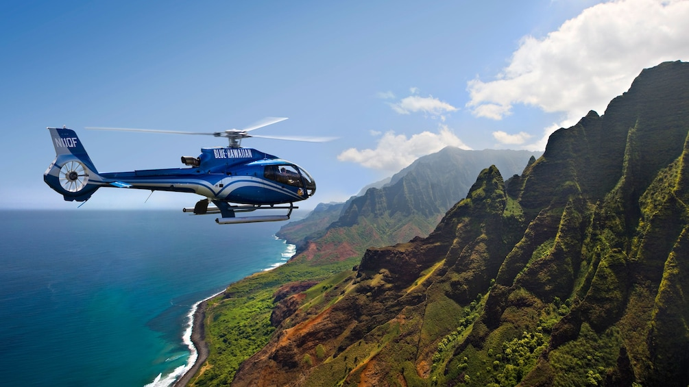Show item 1 of 5. helicopter flying over mountain ridges in Kauai