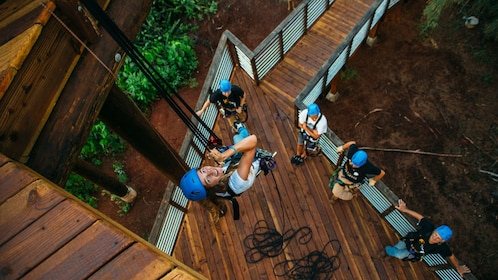 Woman rappelling from platform in Oahu