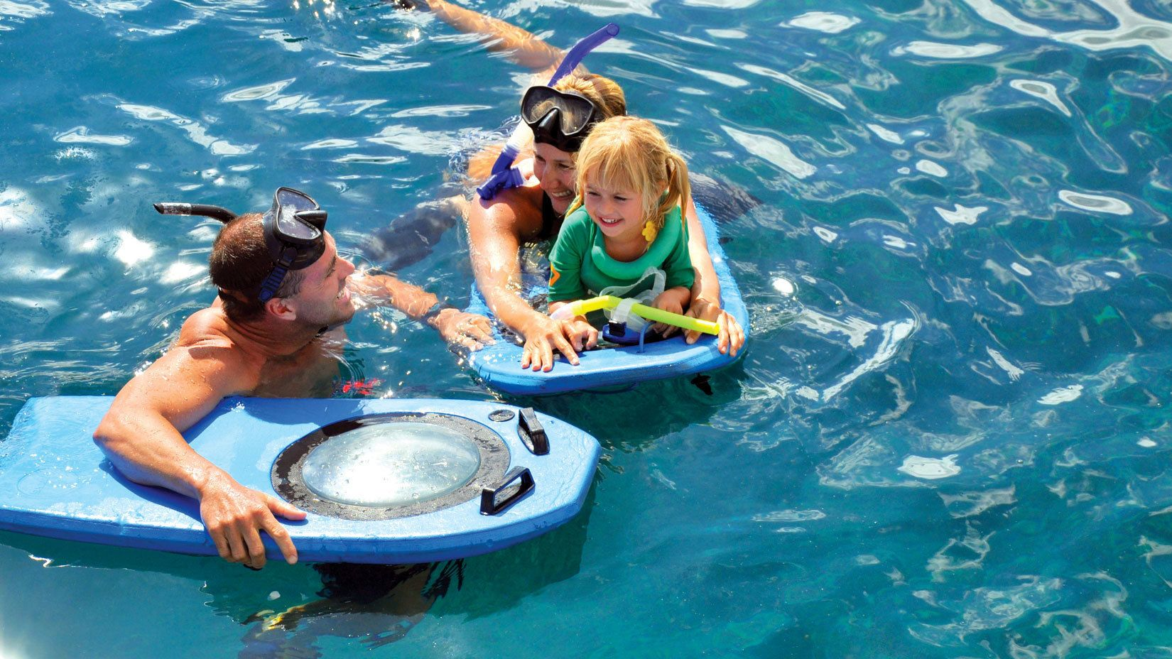 Family with small child snorkeling near Maui