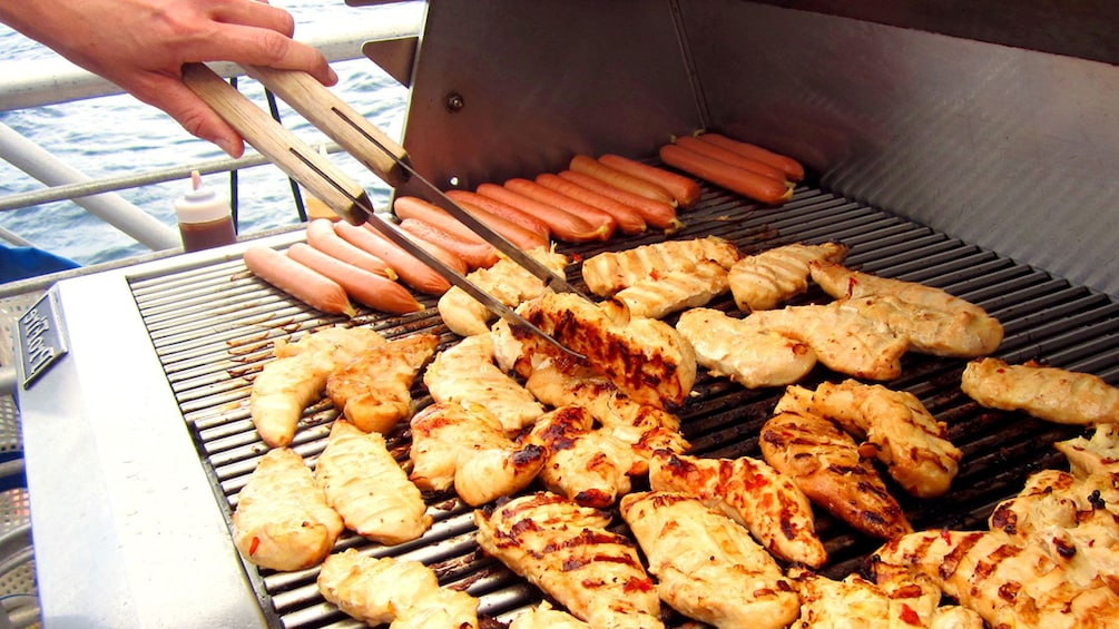Show item 3 of 8. Chef cooking chicken and hotdogs on the grill on the  Molokini Wild Side Eco Adventure in Maui