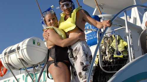 Couple wearing life jackets on deck of boat in Oahu