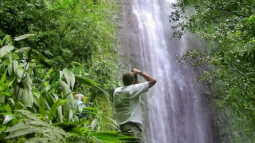 Man taking photo of waterfall surrounded by lush greenery on Oahu
