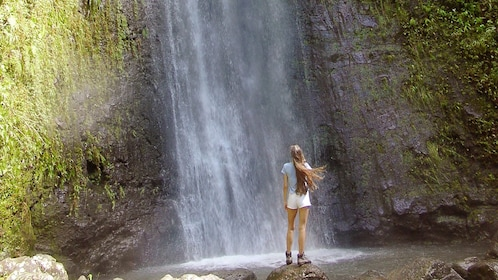 Woman standing on a rock at the bottom of a waterfall in Manoa Falls on Oahu