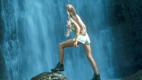 Woman standing on a rock in front of a waterfall on Oahu
