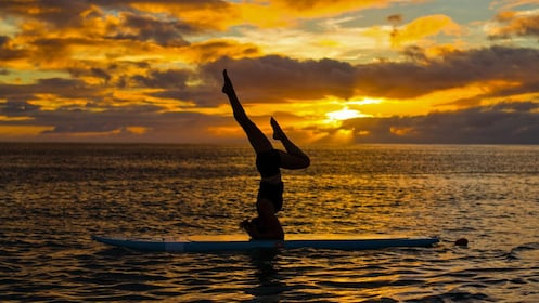 Yoga headstand on paddle board in Oahu