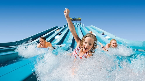 Family going down water slide on their bellies