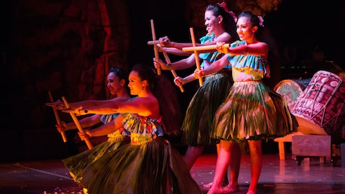 Performers on stage with sticks for the Drums of the Pacific Luau in Maui