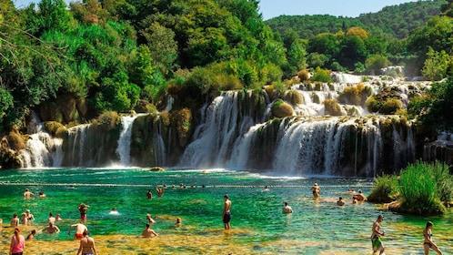 Men and women hang out in Krka Waterfalls