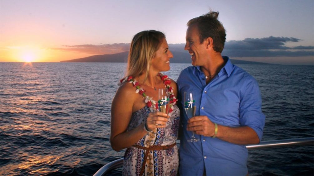 Show item 4 of 5. Couple toasting champagne on sailboat at sunset in Maui