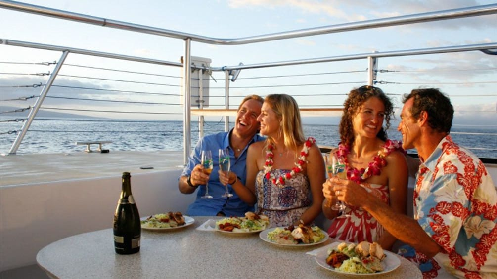 Show item 3 of 5. Dining group on a sailboat at sunset on Maui
