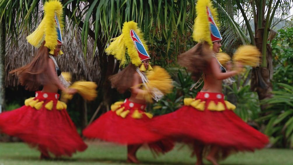 Show item 2 of 5. three Hula dancers at luau in Kauai