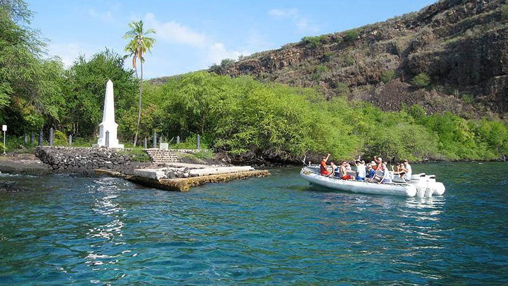 Boat full of people pulling up to a monument on the shore of Hawaii