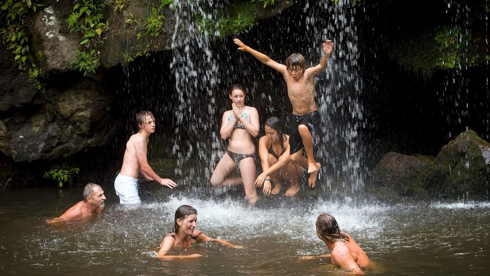 Show item 3 of 5. People splashing around in a waterfall in Hawaii