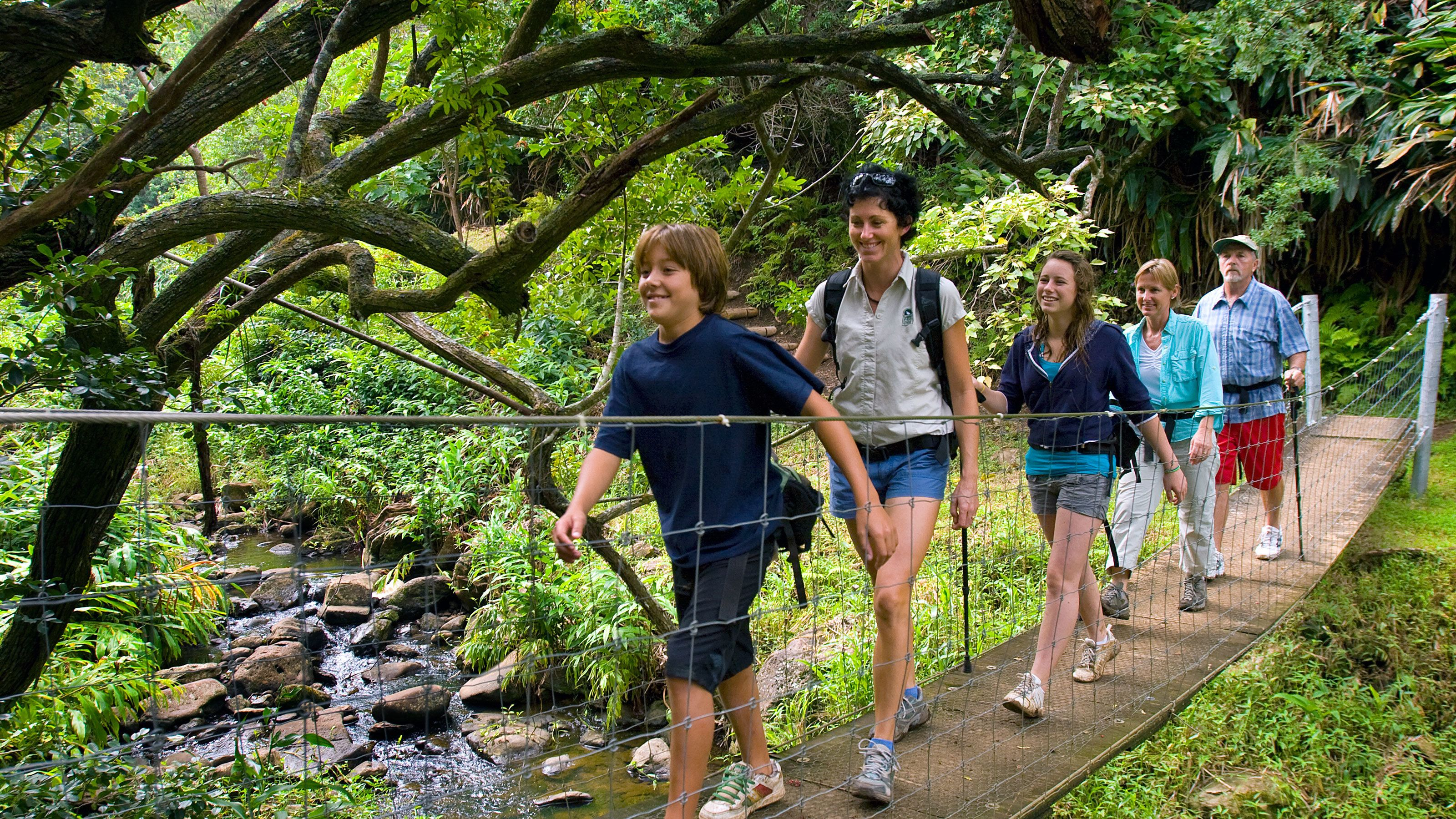 Group crossing over stream on a wooden bridge in Hawaii