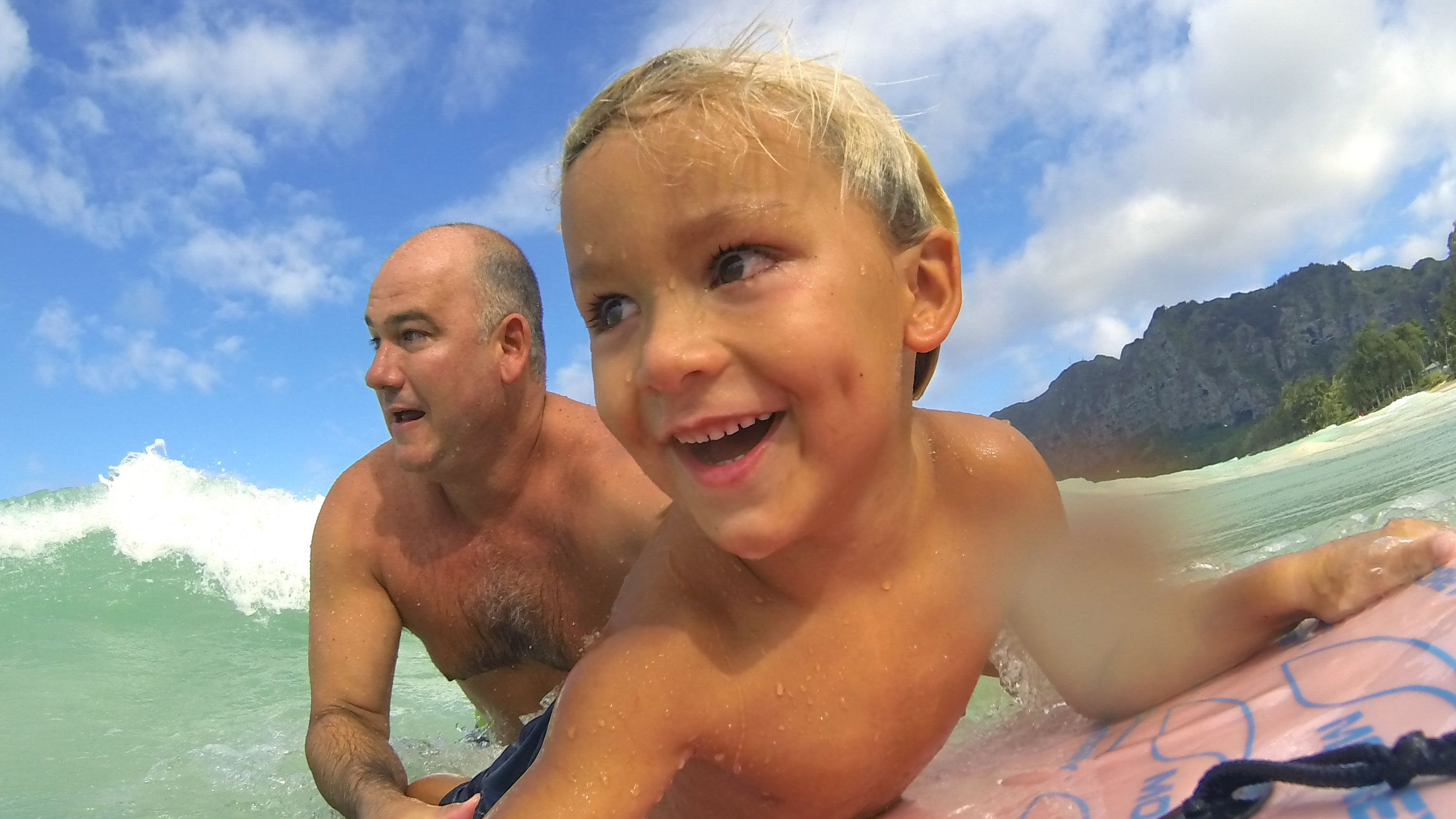 Boy and father on surf board in Kauai