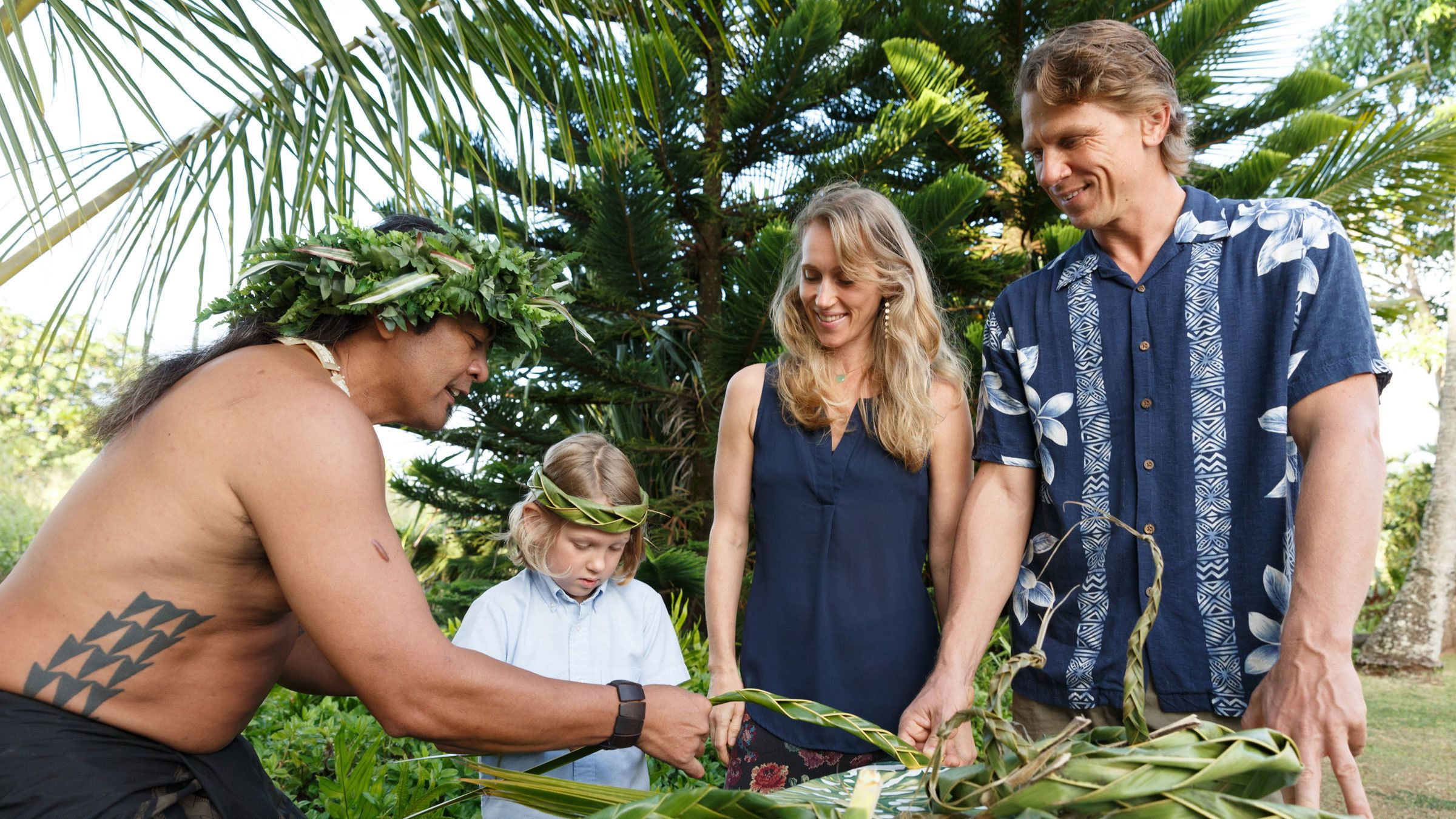 man instructing young boy in how to weave palm leaves in Kauai