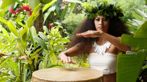 Woman in traditional clothing plays drum in Kauai