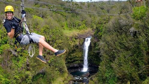 male ziplining over waterfall in hawaii