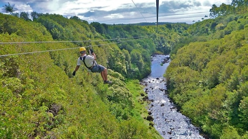 person ziplining over a stream of water in hawaii