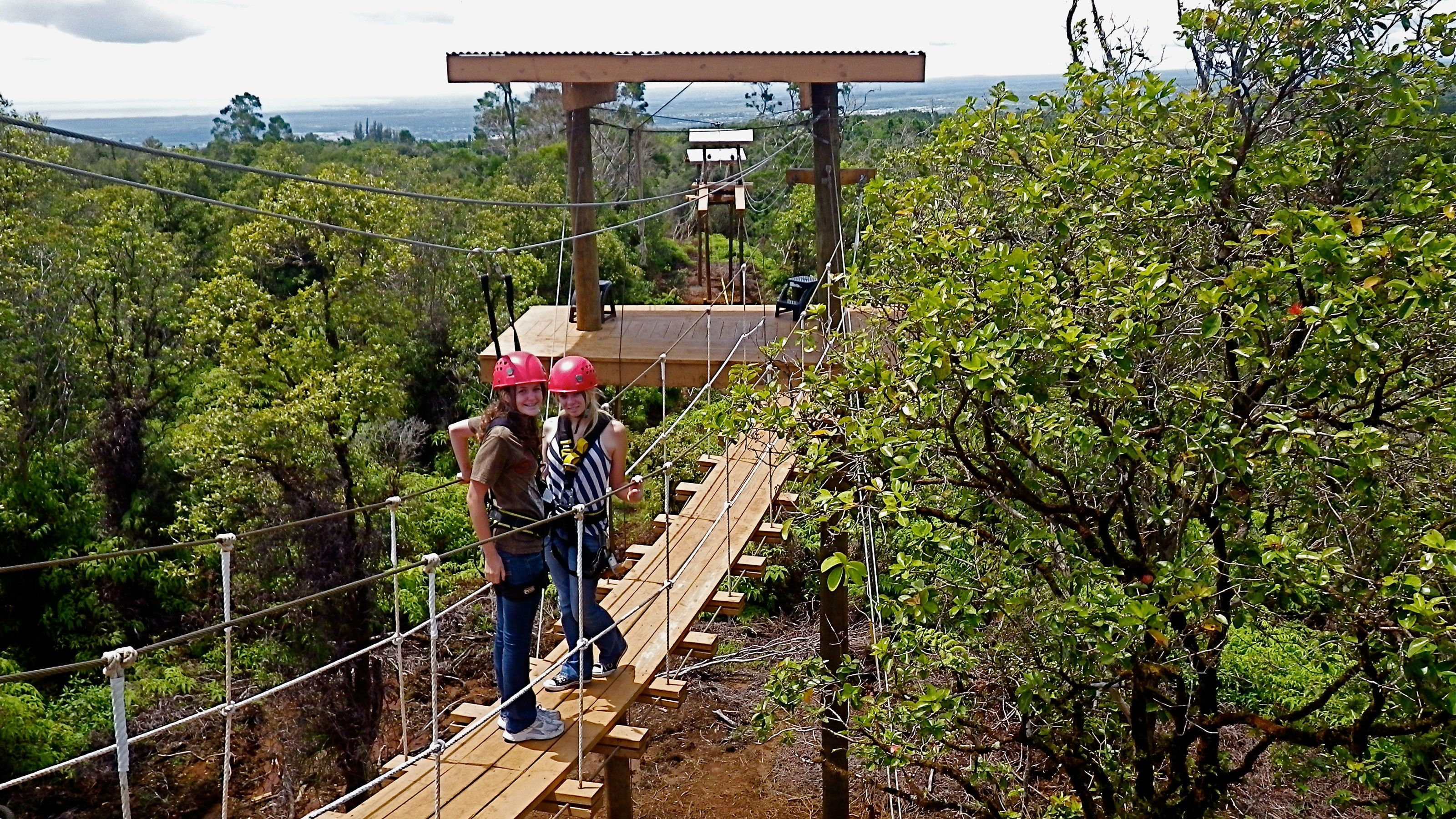 two young ladies on a bridge to the ziplining station in hawaii