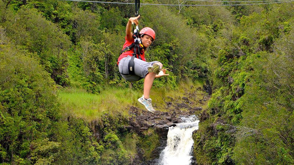 Person on a zip line above a Hawaiian waterfall and forest
