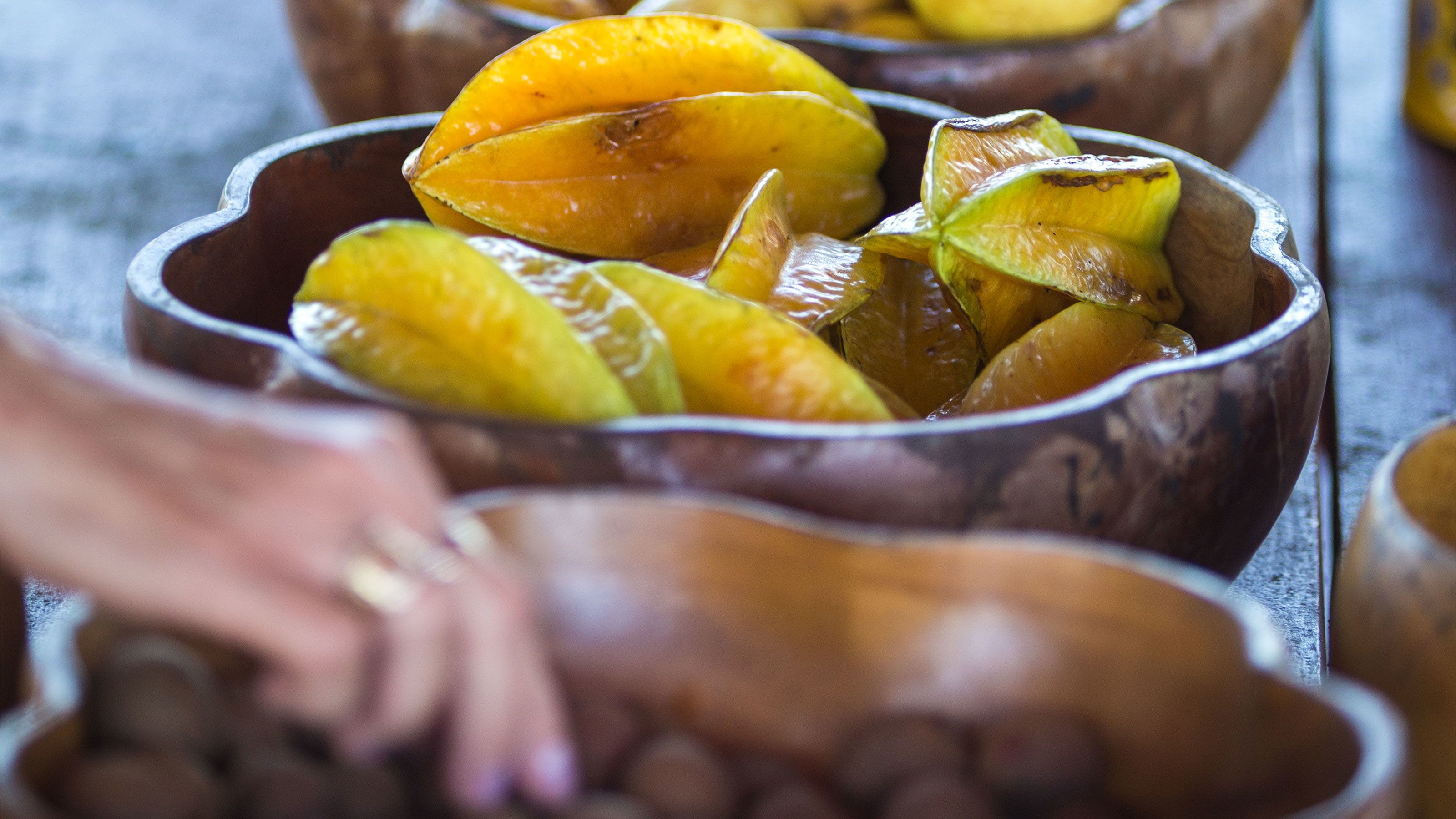 A wooden bowl of star fruit