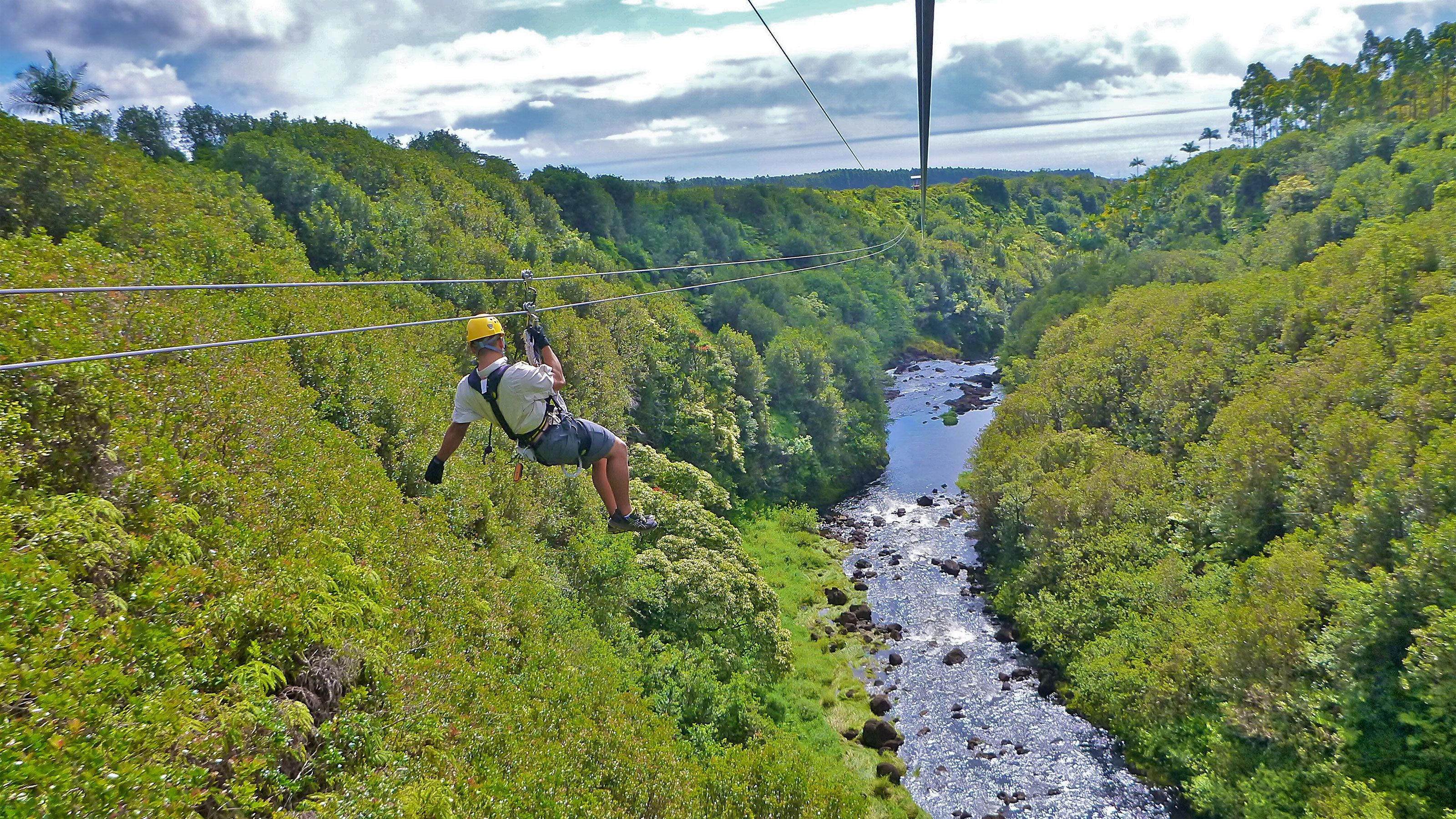 Ziplining man over a waterfall on the Big Island of Hawaii