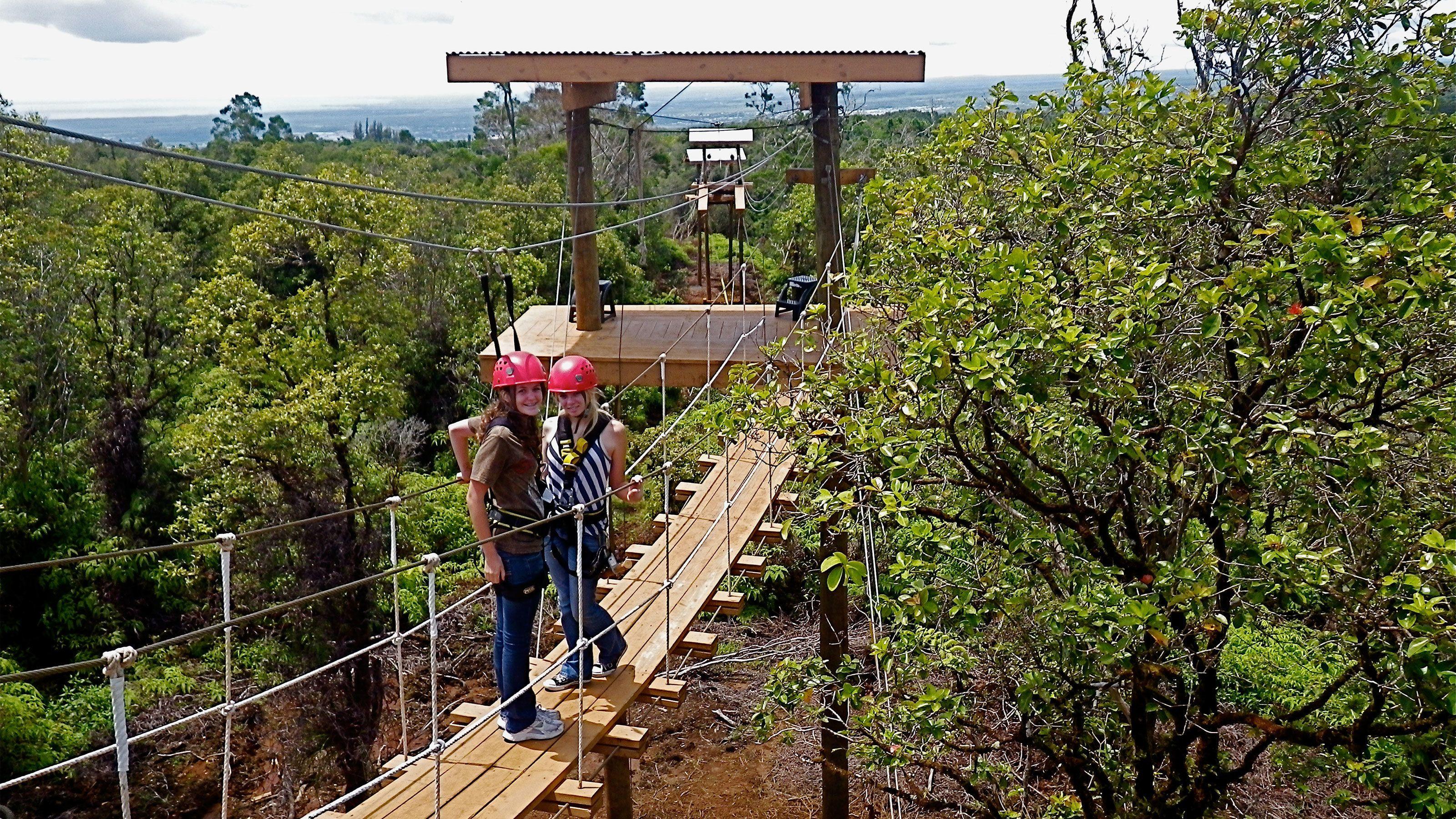 Two women on an zip line bridge in a canopy of a Hawaiian forest