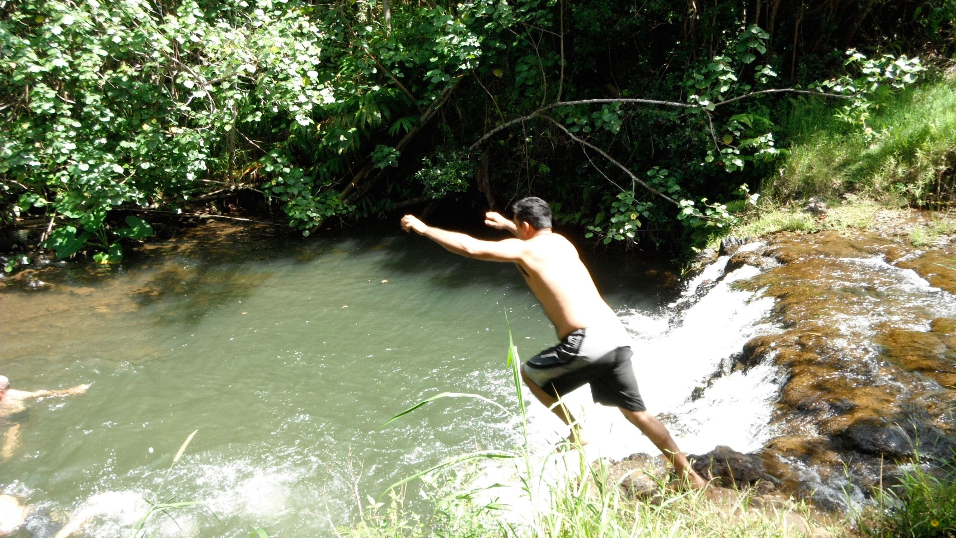 man jumping into pond from rock in Kauai