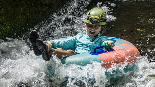 young boy riding in a tube on river in Kaua