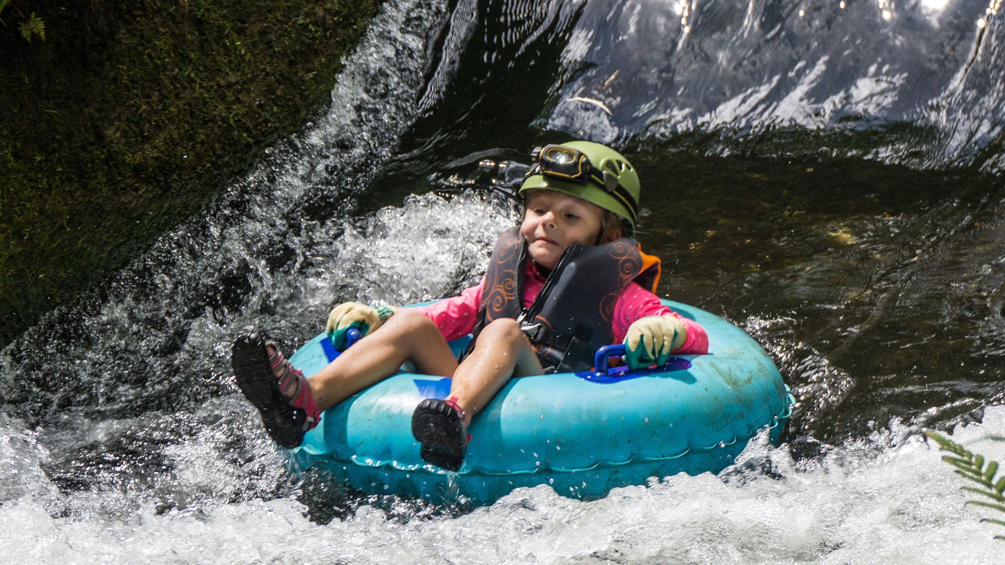 young girl riding in a tube on river in Kauai