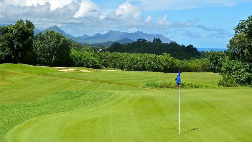 Show item 3 of 5. Golf green in foreground with mountains in view at Ko'olau Golf Club