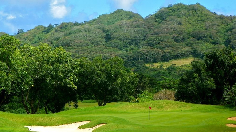Show item 2 of 5. Lush green hills surround a golf hole at Ko'olau Golf Club