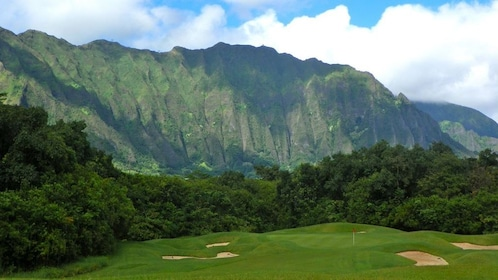 Dramatic cliffs rise behind a golf green at Ko'olau Golf Club