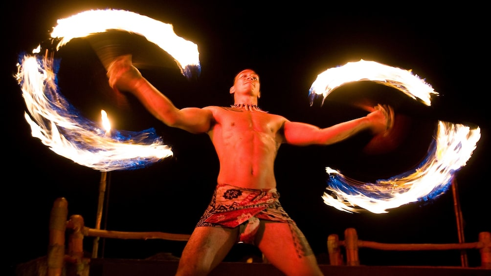 Show item 1 of 10. Male swing fire in the Te Au Moana Luau performance in Maui