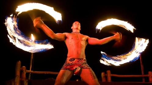Male swing fire in the Te Au Moana Luau performance in Maui