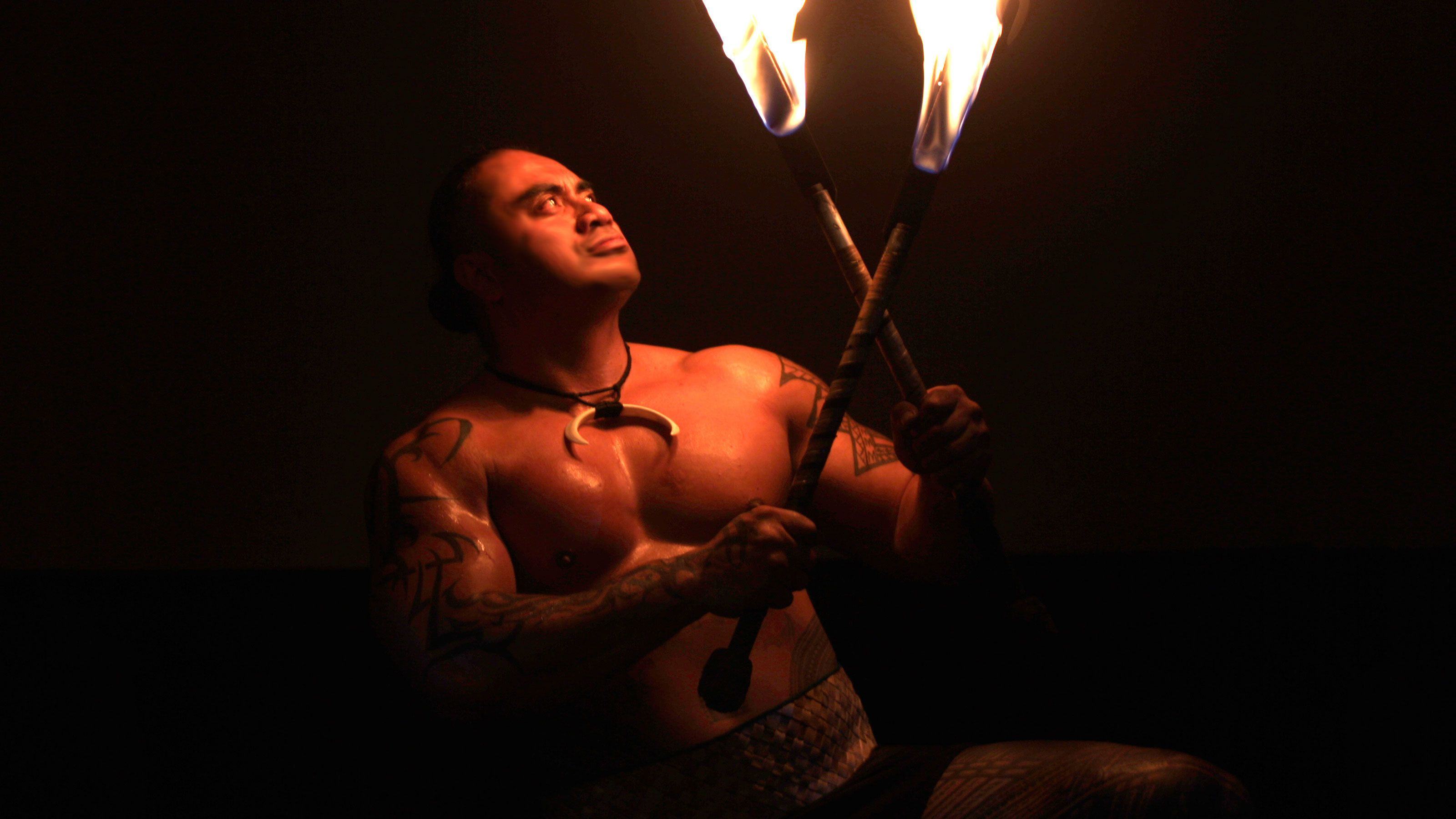 Guy in Te Au Moana Luau performance with fire in Maui