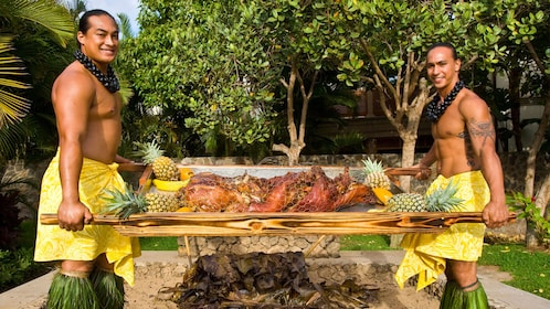 Two males in performance outfits with a roasted pig for the Te Au Moana Luau in Maui