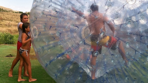 daughters pushing father in an aquaball in Maui